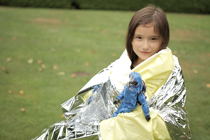 "Sofia Boerma, participant in the 2013 August  Decontamination Drill, is wrapped up in an emergency thermal blanket with the ""Decon Doll""."