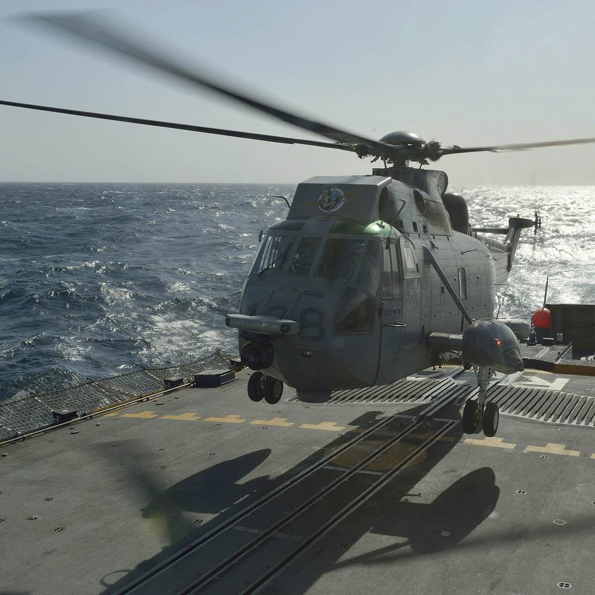 A Sea King helicopter lands on the flight deck of a Royal Canadian Navy ship.