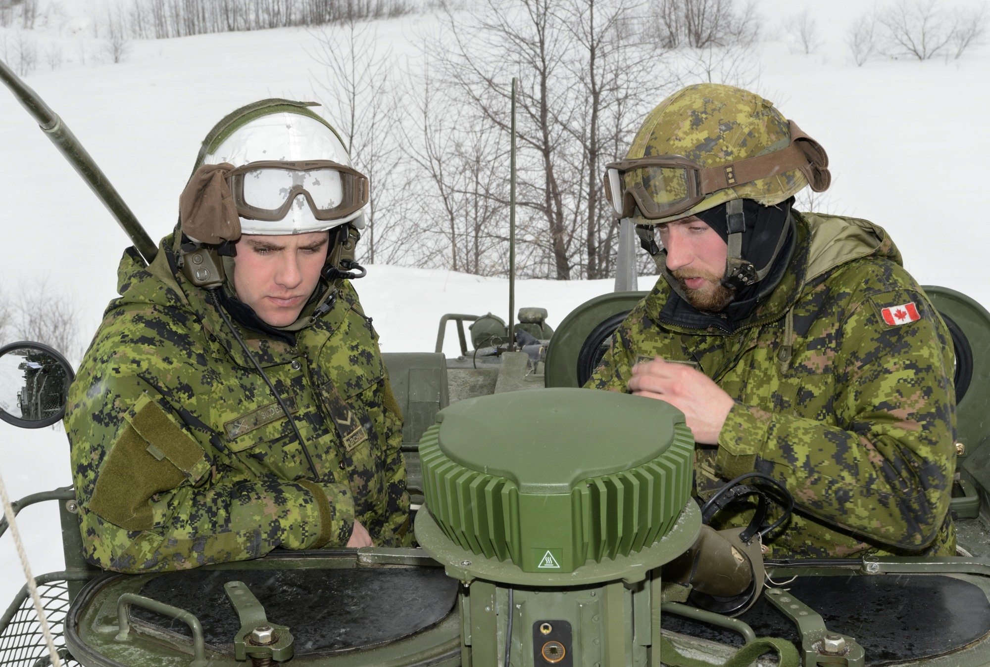 Two Canadian Armed Forces members on a LAV-III during the trial of the GAJT-700M GPS Anti-Jammer antenna, pictured in centre.