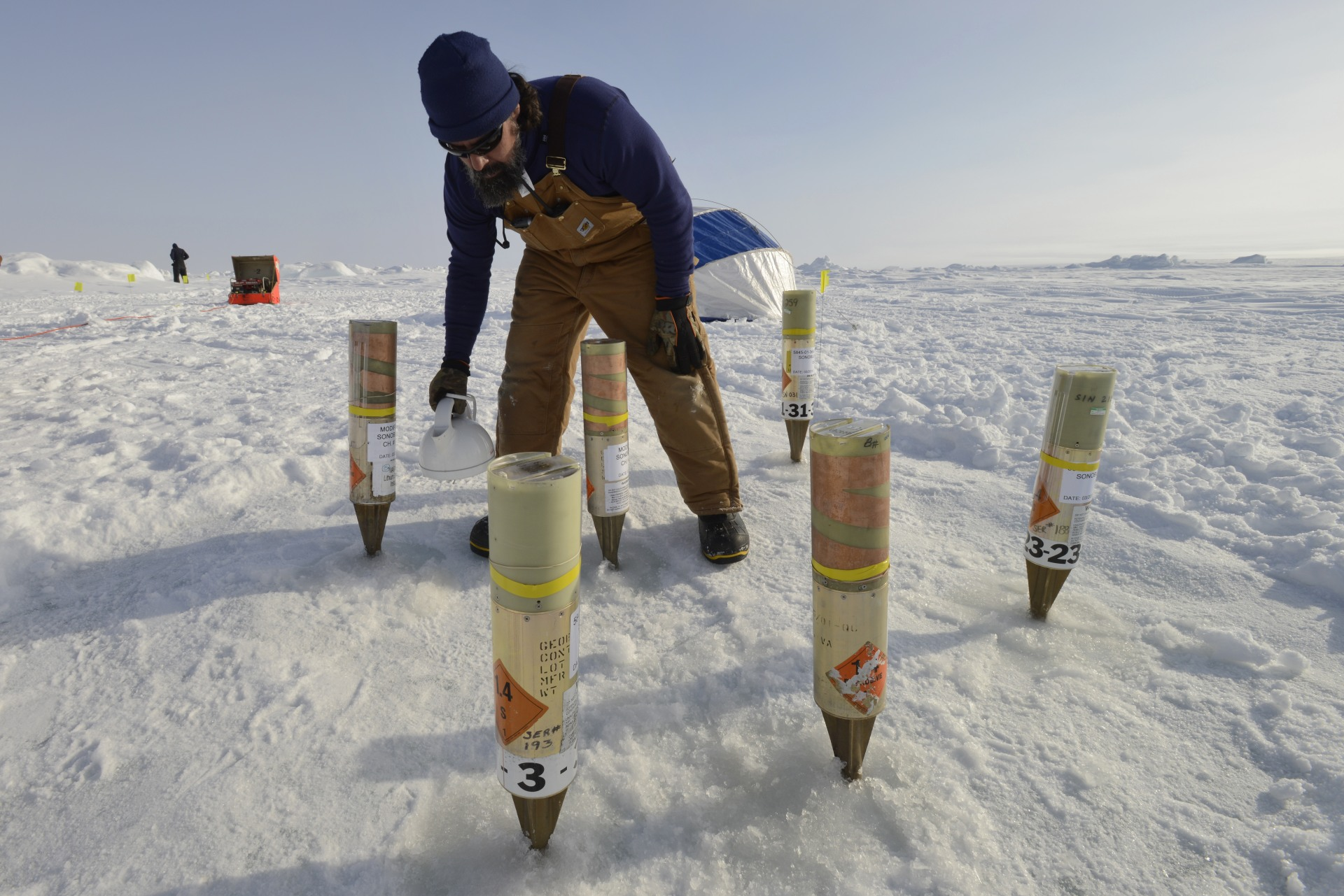 Watering a geobuoy garden. The buoys were inserted with the entire icepick embedded in the holes, then a slurry of ice and water was poured around the holes and allowed to freeze, coupling the geobuoys to the ice in a controlled manner.
