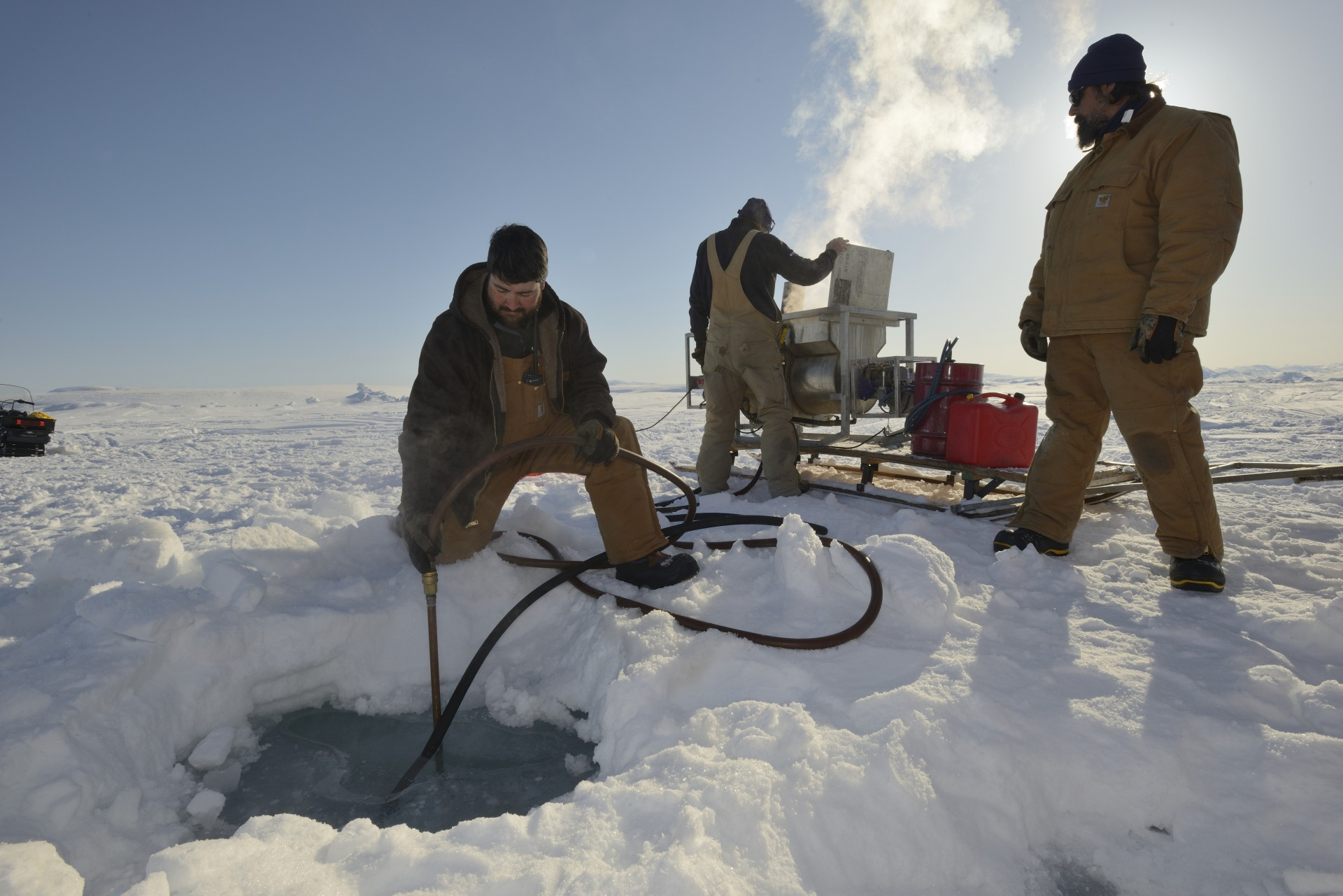 A hot water drill is sometimes used to drill larger holes in the ice.