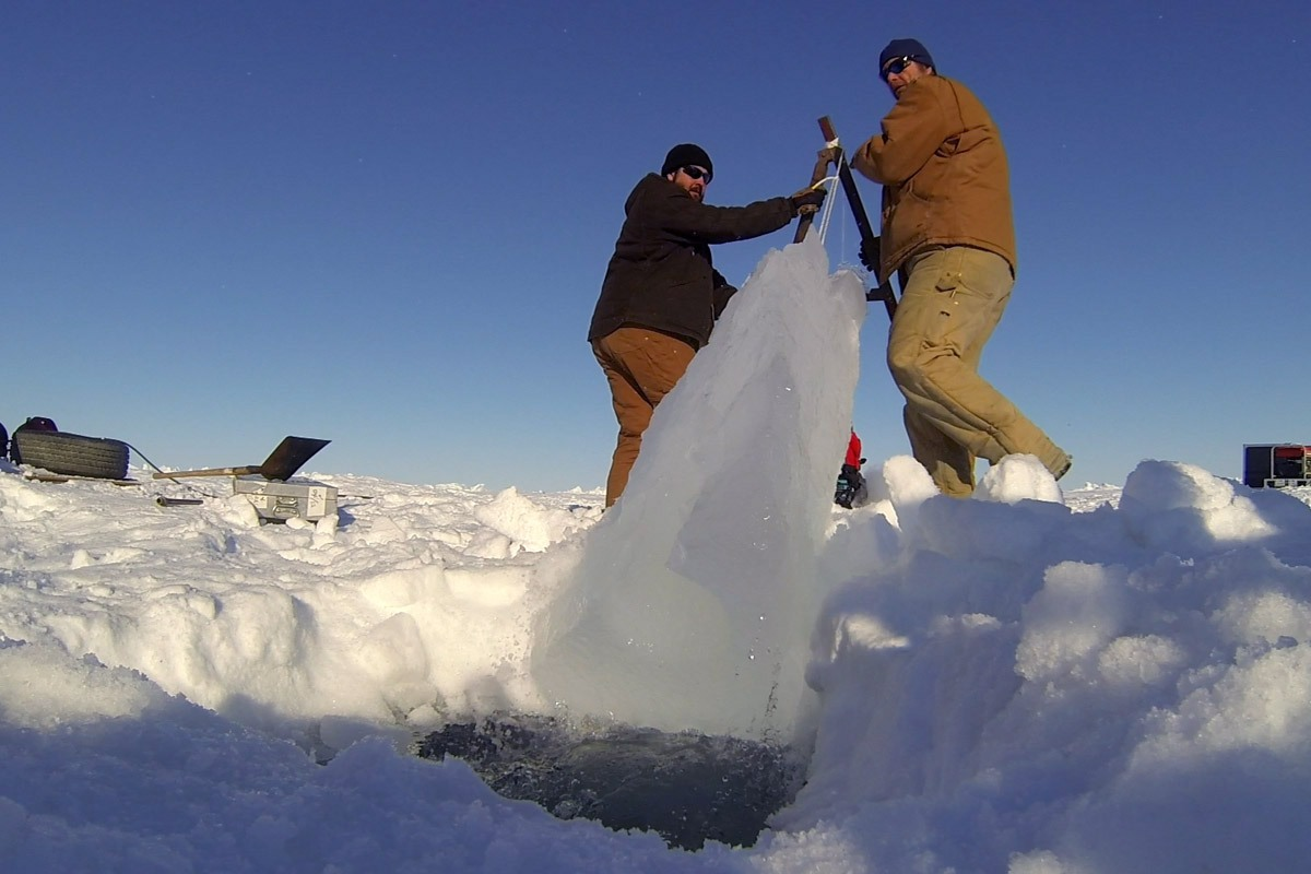 A snowmobile and a rope make it easier to remove a heavy ice block.