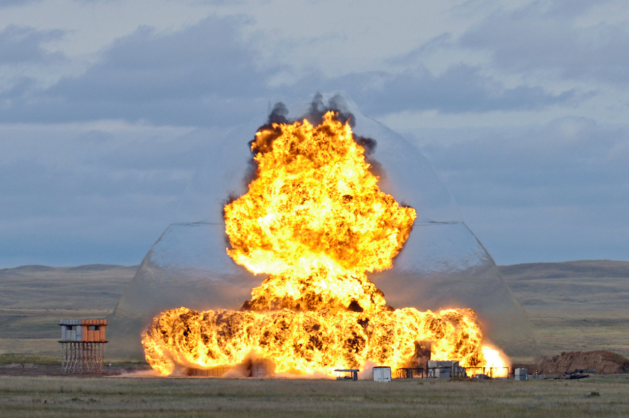 A large burst of flames and shock wave engulfs a series of concrete structures built for an explosives trial on the Experimental Proving Ground at DRDC – Suffield Research Centre.