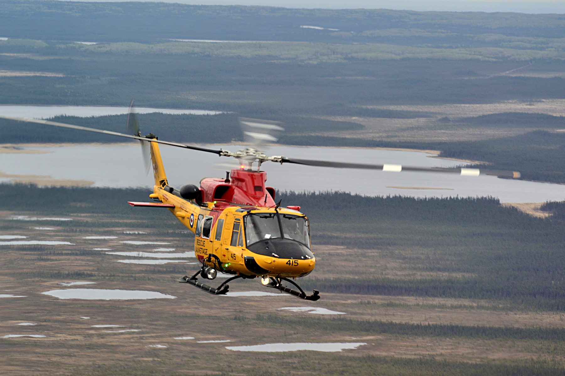A CH-146 Griffon helicopter from 417 Search and Rescue Squadron based in Cold Lake, Alberta conducts operations over northern Alberta while providing assistance to the province during wildfires near Fort McMurray on May 9, 2016. Photo: MCpl Brandon O'Connell, 3 CDN DIV PA