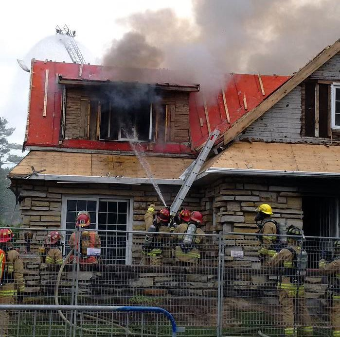 This photo shows a house that appears to be on fire. There is no flame visible, but lots of smoke is coming out of the second floor window. There are nine firefighters in the picture, several observing the fire, and three pointing a hose at the window and shooting a stream of water into it.