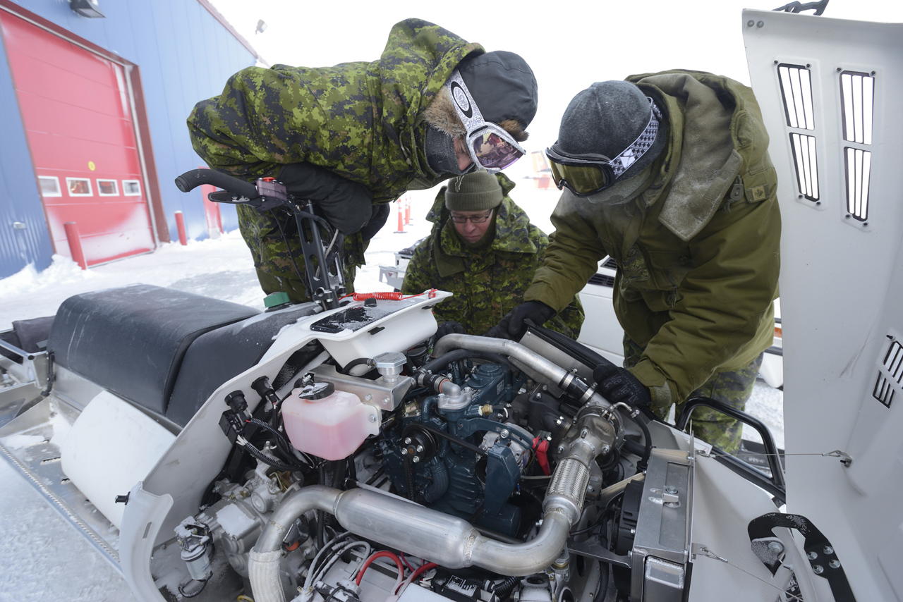 Defence Research and Development Canada and Canadian Armed Forces Joint Arctic Experiment (CAFJAE) 2016 team member Sergeant Rob Kubiak (center) gives a training session on the DEW D900 diesel snowmobile to 2nd Battalion, the Royal Canadian Regiment members.