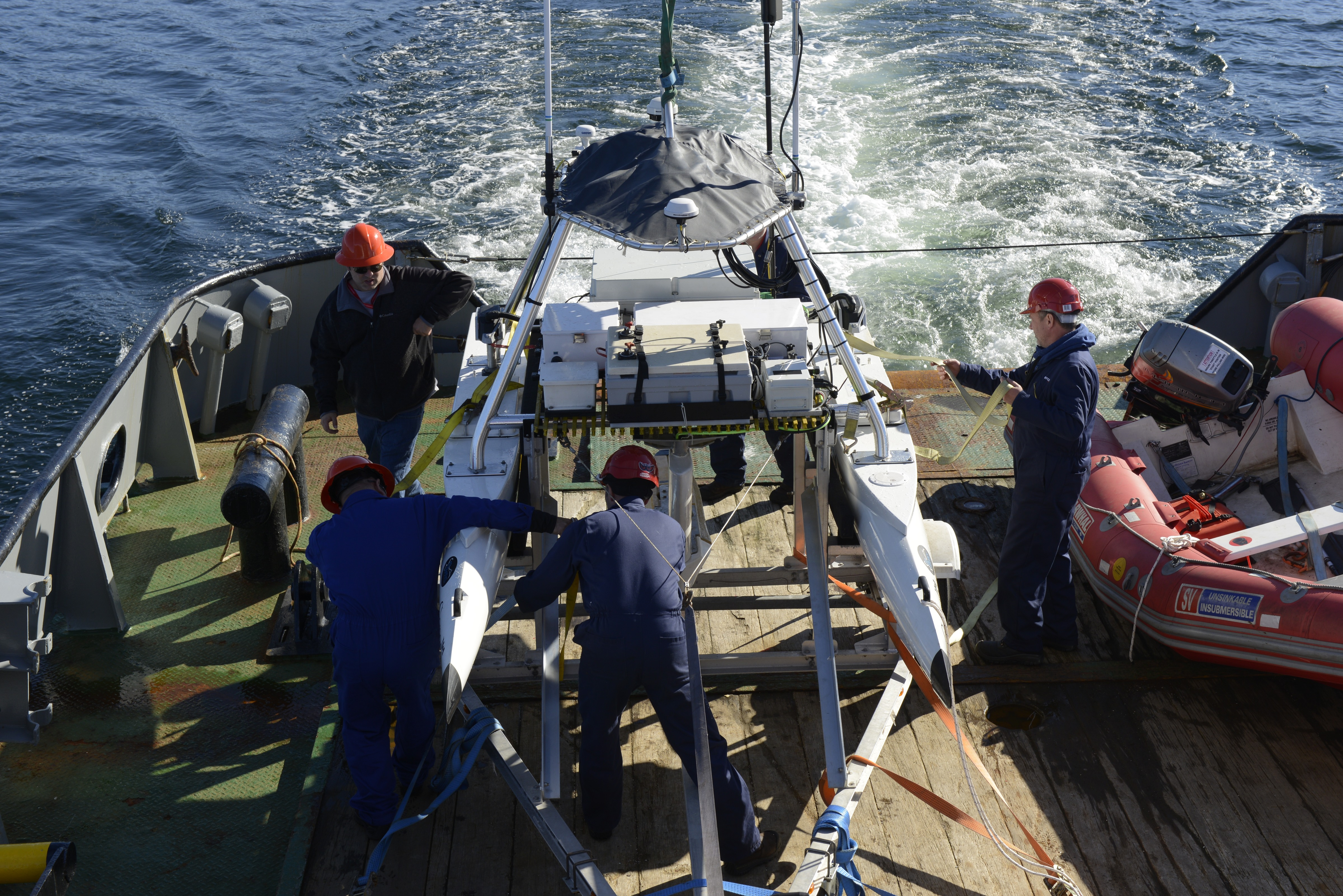 Defence Research and Development Canada technologists and ship crew secure their USV-2600 unmanned surface vehicle on the SD Kyle of Lochalsh ship after completing a mission in Belmacara Bay. Photo by Janice Lang, DRDC