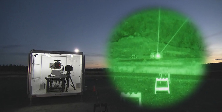 DRDC's high energy laser (HEL) mobile laboratory at 2nd Canadian Division Support Base Valcartier at sunset. The inset shows a night vision depiction of green aiming lasers.