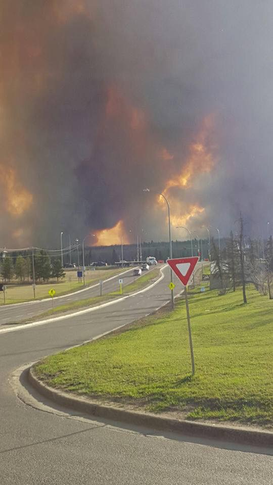 This is a picture of fire and thick dark smoke as seen in the distance from a highway. It was taken on May 1st, 2016, at the beginning of the Fort McMurray wildfire.