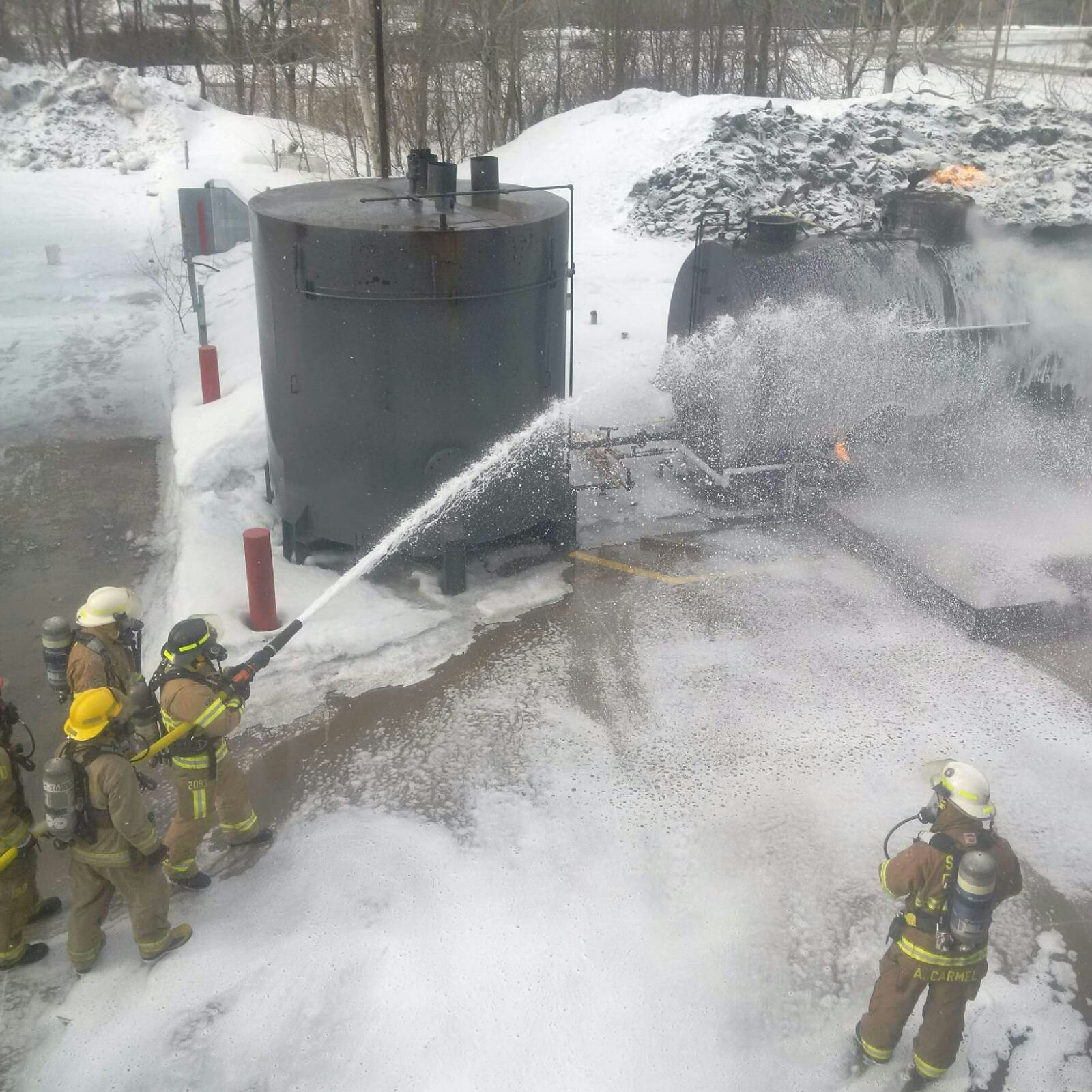 Firefighters use foam to extinguish crude oil fire.
