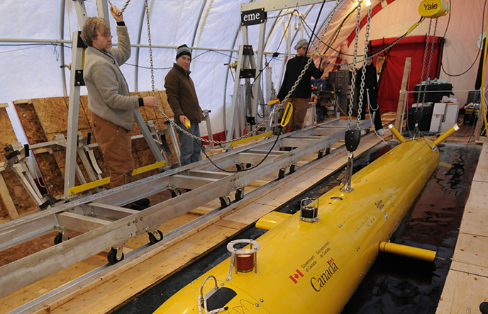An Autonomous Underwater Vehicle (AUV) is raised out of the Arctic ice using a gantry system.